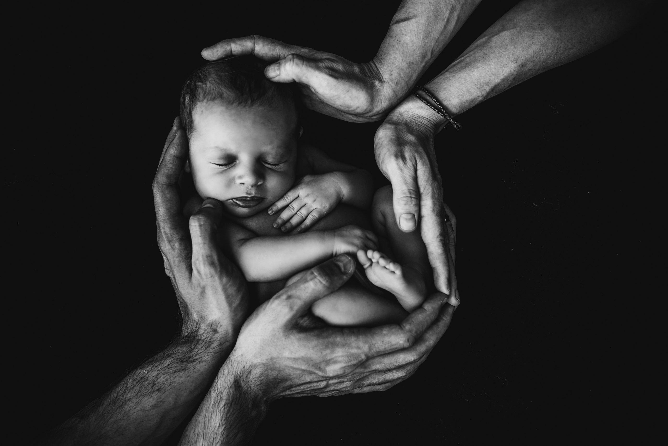 bébé entouré de mains de personnes plus âgées (noir et blanc)