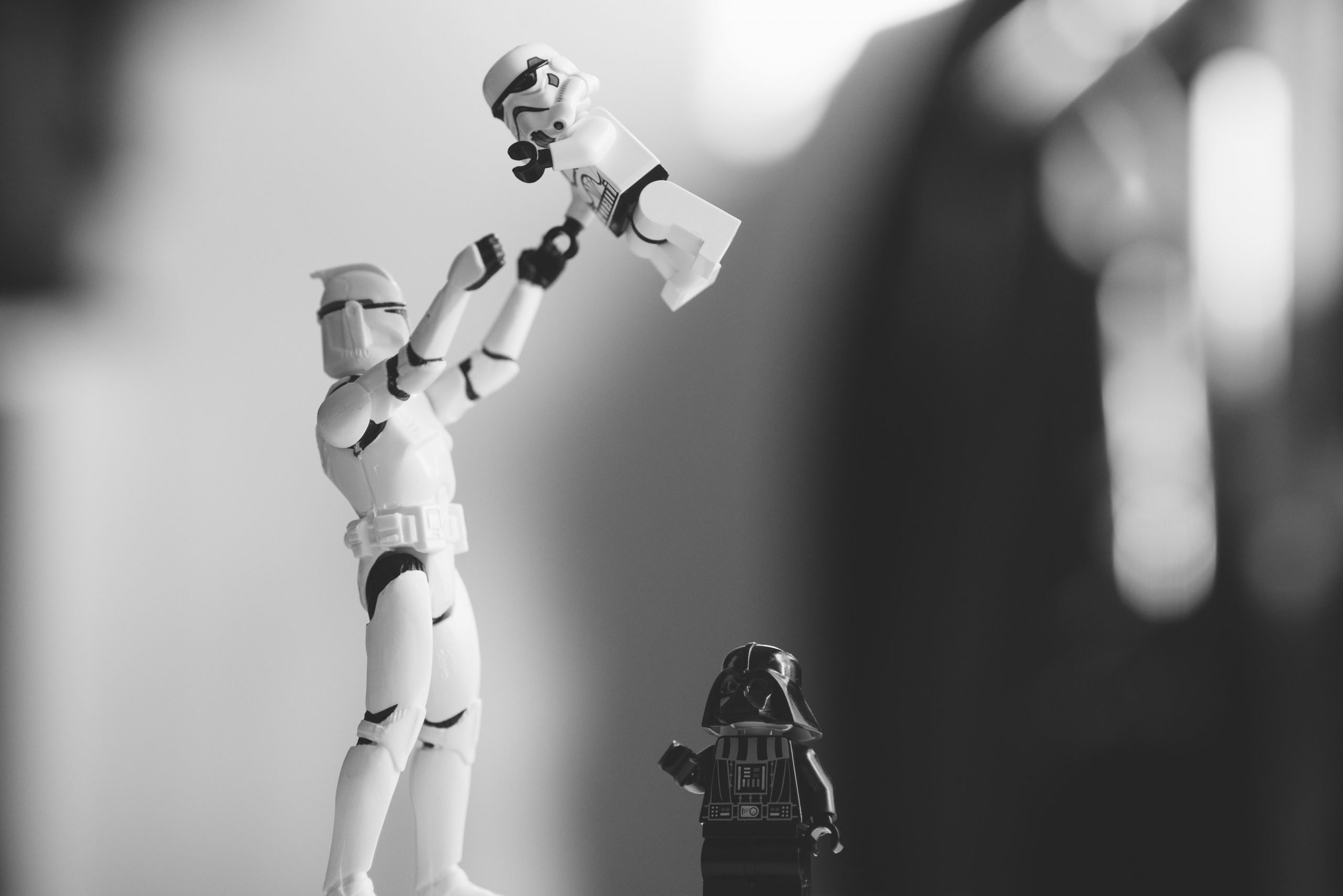 Un clone jette en l'air un enfant clone avec un tout petit Darth Vador à ses pieds (en Lego)