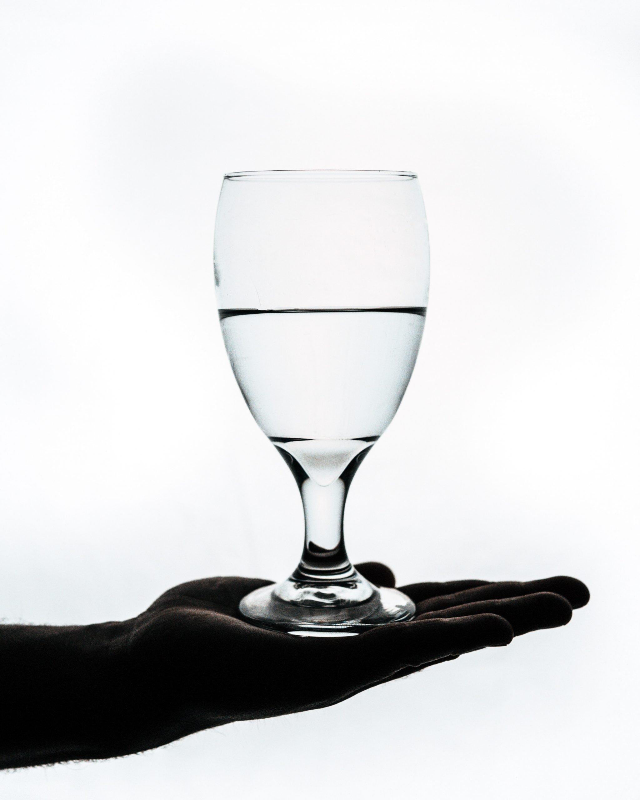 verre à moitié plein posé sur une main