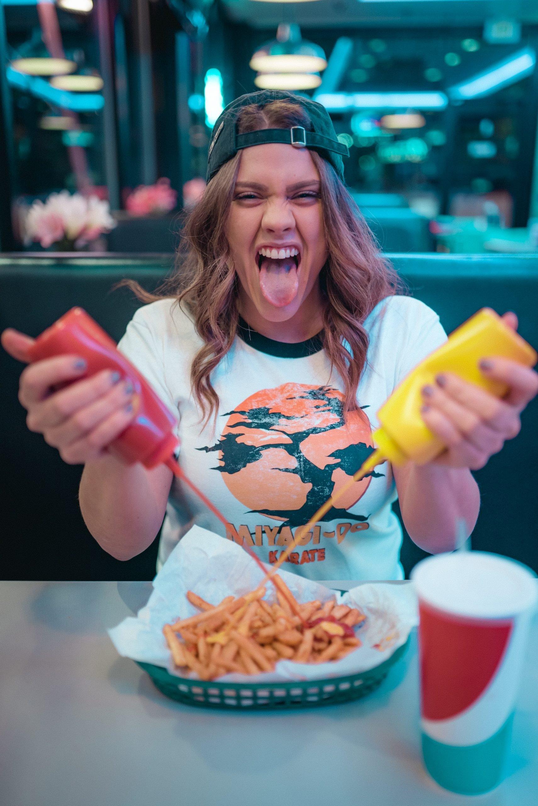 Fille qui presse ketchup et moutarde sur des frites (et qui tire la langue)